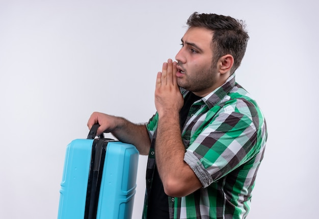 Young traveler man in checked shirt holding suitcase telling a secret with hand near his mouth standing sideways white wall