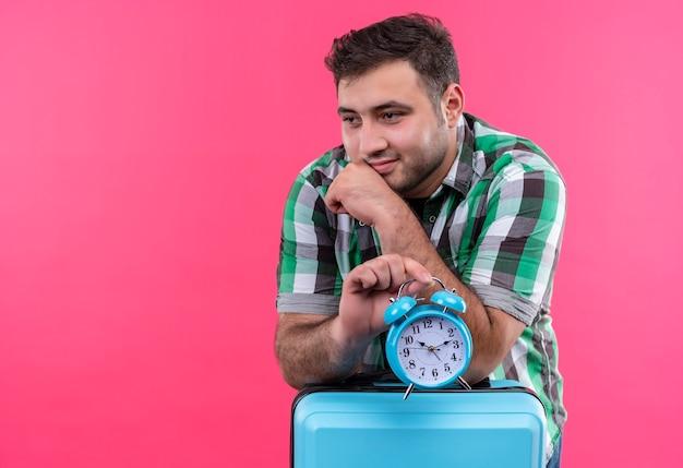 Uomo giovane viaggiatore in camicia controllata che tiene la valigia con sveglia che osserva da parte con sguardo sognante in piedi sopra la parete rosa