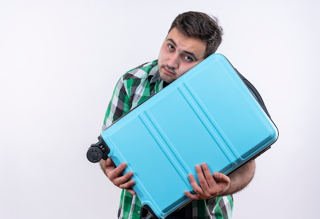 Uomo giovane viaggiatore in camicia controllata che tiene la valigia con l'espressione triste sul viso in piedi sopra il muro bianco