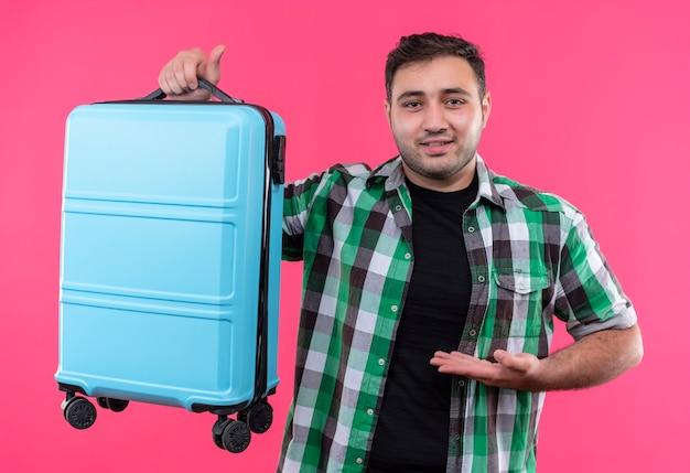 Uomo giovane viaggiatore in camicia a quadri che presenta la sua valigia con il braccio sorridente fiducioso in piedi oltre il muro rosa