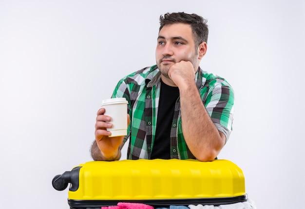 Uomo giovane viaggiatore in camicia a quadri in piedi con la valigia piena di vestiti che tengono la tazza di caffè che osserva da parte pensando sopra il muro bianco