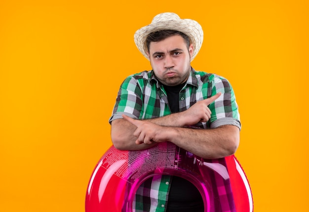 Giovane viaggiatore uomo in camicia a quadri e cappello estivo azienda anello gonfiabile dispiaciuto soffiando guance rivolte con le dita ai lati in piedi sopra la parete arancione