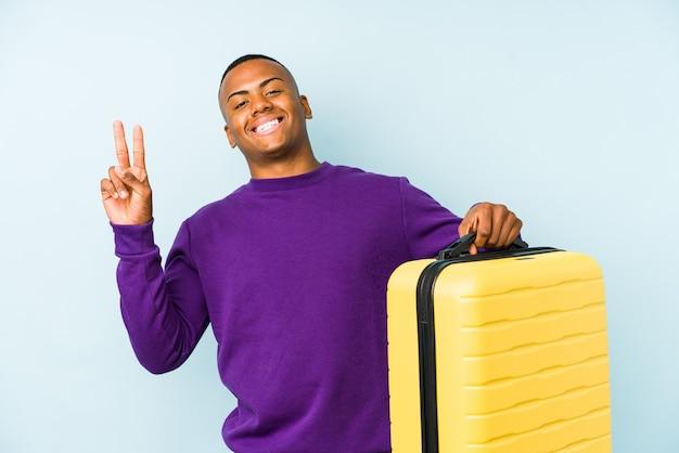 젊은 여행자 남자 가방을 들고 손가락으로 평화의 상징을 보여주는 즐겁고 평온한 고립.