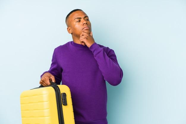 의심스럽고 회의적인 표정으로 옆으로 보이는 가방을 들고 젊은 여행자 남자.