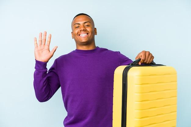 Молодой путешественник человек, держащий чемодан, изолировал улыбаясь веселый показ номер пять с пальцами.