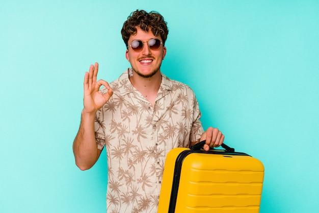 쾌활하고 자신감이 확인 제스처를 보여주는 파란색 배경에 노란색 가방을 들고 젊은 여행자 남자.