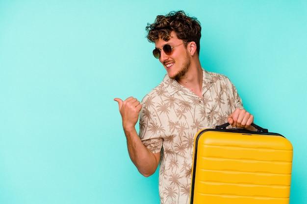 青い背景に黄色いスーツケースを持っている若い旅行者の男は、親指の指を離れて、笑ってのんきなポイント。
