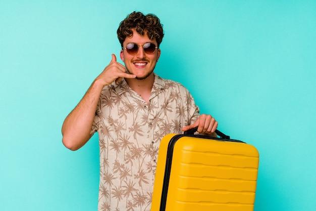 指で携帯電話の呼び出しジェスチャーを示す青い壁に黄色のスーツケースを保持している若い旅行者の男性。