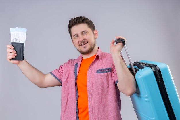 Молодой путешественник мужчина держит авиабилеты и чемодан, глядя в камеру, улыбаясь со счастливым лицом, стоящим на изолированном белом фоне