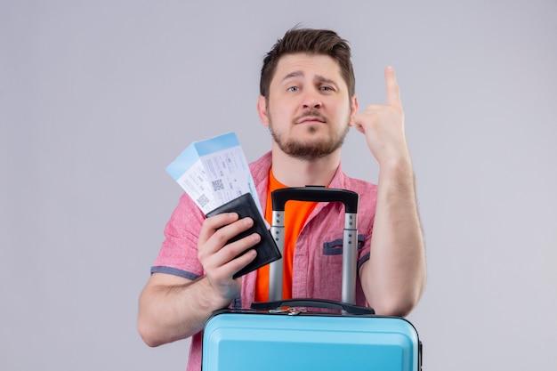 Молодой путешественник, держащий авиабилеты и чемодан, выглядит уверенно, указывая пальцем вверх, стоя на изолированном белом фоне