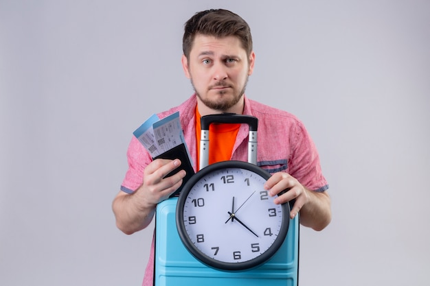 Молодой путешественник мужчина держит авиабилеты и чемодан с часами, глядя в камеру с серьезным уверенным выражением лица, стоящим на изолированном белом фоне