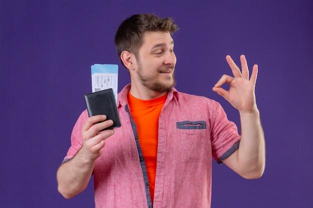 紫色の背景の上に立ってokサインをやって笑ってよそ見航空券を保持している若い旅行者男