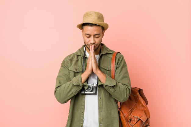 Young traveler man holding hands in pray near mouth, feels confident