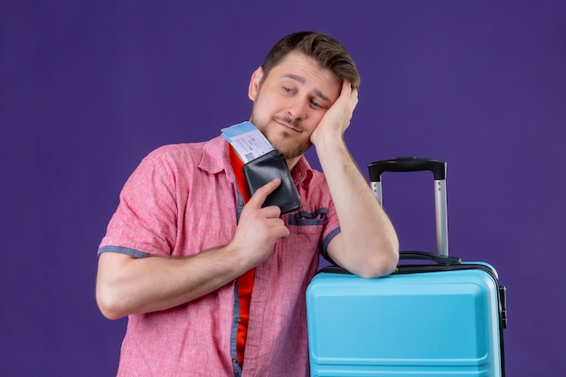 Young traveler man holding suitcase and air tickets looking aside with sad expression on face standing over purple background