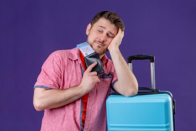 Молодой путешественник мужчина держит чемодан и авиабилеты, глядя в сторону с грустным выражением лица, стоящего на фиолетовом фоне