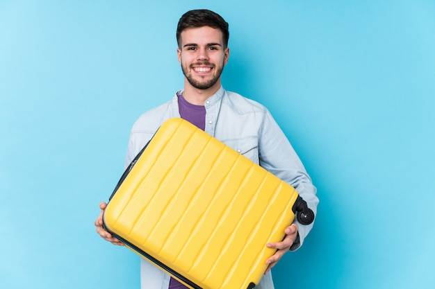Young traveler man holding a suitcase happy, smiling and cheerful