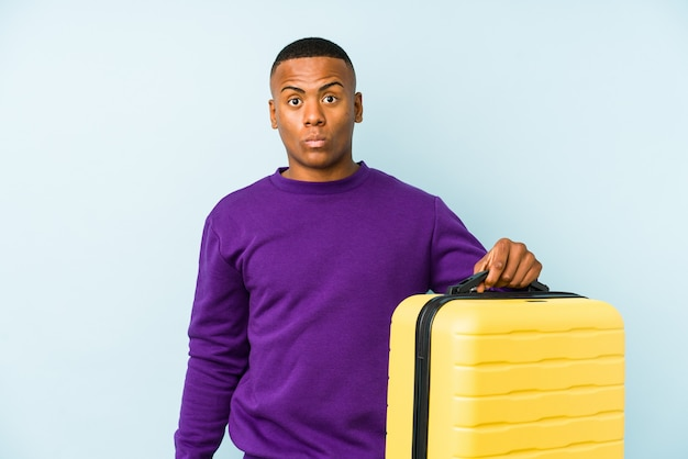 Young traveler man holding a suitcase isolated shrugs shoulders and open eyes confused.
