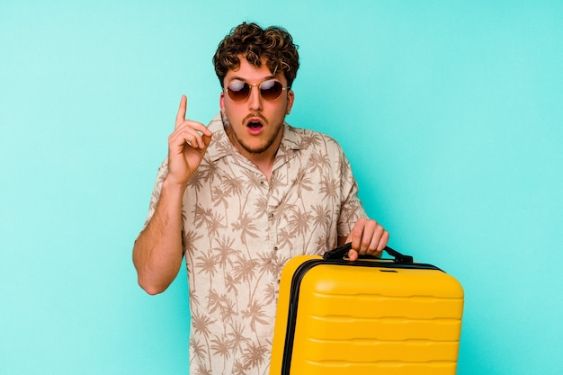 Young traveler man holding a yellow suitcase on blue background having an idea, inspiration concept.