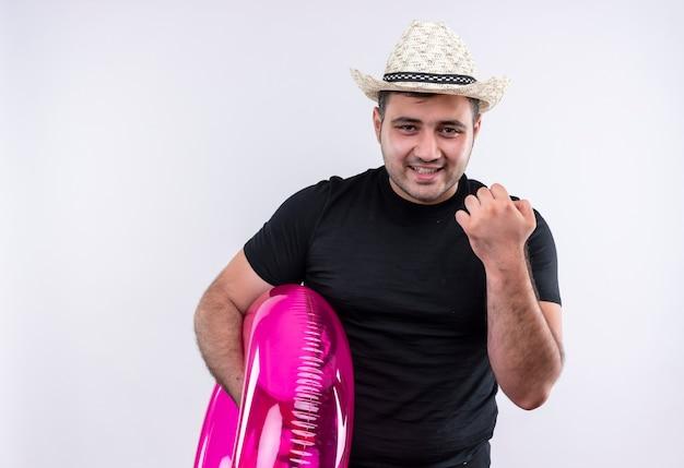 黒のtシャツと夏の帽子をかぶった若い旅行者の男性が幸せで前向きに膨らませてリングを保持し、白い壁の上に元気に立って笑っている