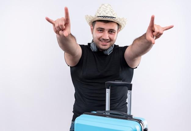 白い壁の上に元気に立って笑顔の指で岩のシンボルを作るスーツケースと黒のtシャツと夏の帽子の若い旅行者の男