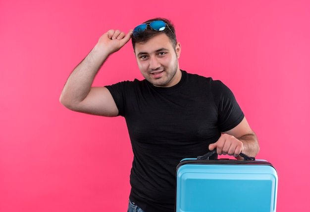 ピンクの壁の上に立っている顔に笑顔で幸せでポジティブなスーツケースを保持している黒いtシャツの若い旅行者の男
