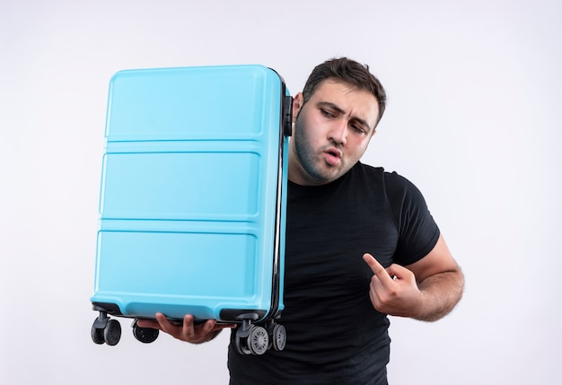 검지 손가락으로 가리키는 가방을 들고 검은 티셔츠에 젊은 여행자 남자가 흰 벽에 불안한 서 옆으로 찾고