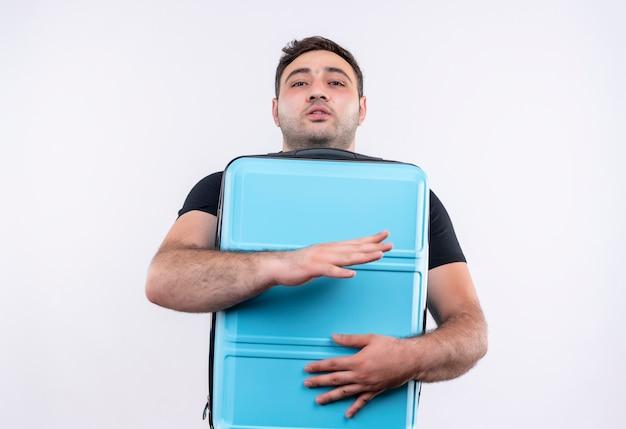 白い壁の上に前向きで幸せなスーツケースを保持している黒いtシャツの若い旅行者の男