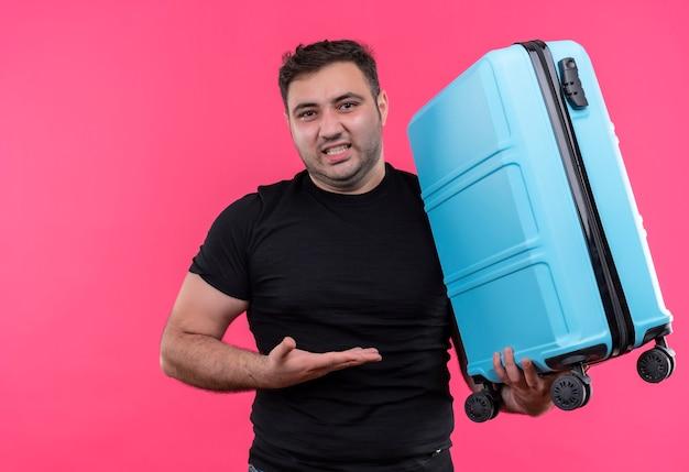 ピンクの壁の上に立っているイライラした表情で彼の手の腕でそれを提示するスーツケースを保持している黒いtシャツの若い旅行者の男
