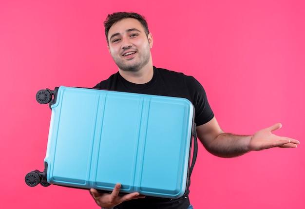 ピンクの壁の上にフレンドリーに立って笑顔のスーツケースを保持している黒いtシャツの若い旅行者の男