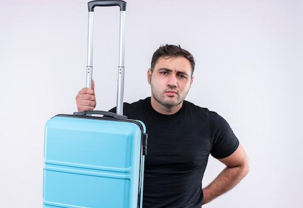 白い壁の上に立っている眉をひそめている顔とスーツケースを保持している黒いtシャツの若い旅行者の男