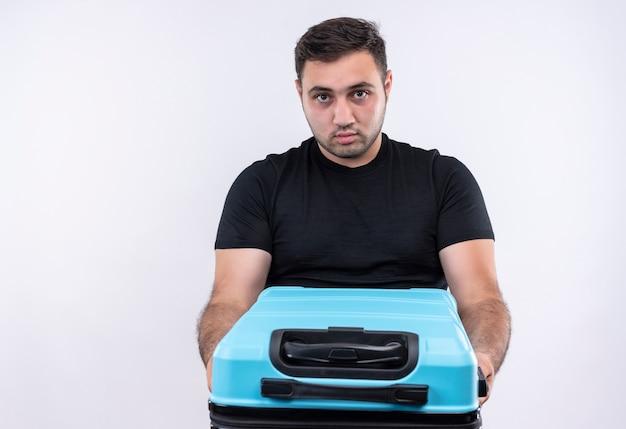 白い壁の上に立っている深刻な顔とスーツケースを保持している黒いtシャツの若い旅行者の男