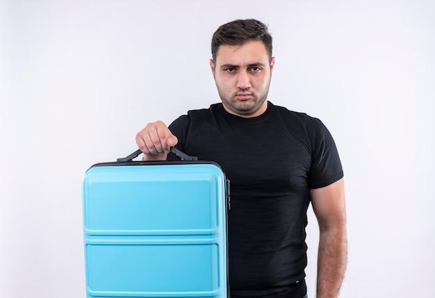 白い壁の上に立っている深刻な眉をひそめている顔とスーツケースを保持している黒いtシャツの若い旅行者の男