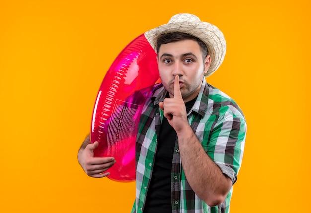 Молодой путешественник в клетчатой рубашке и летней шляпе держит надувное кольцо, делая жест тишины с пальцем на губах, стоя над оранжевой стеной