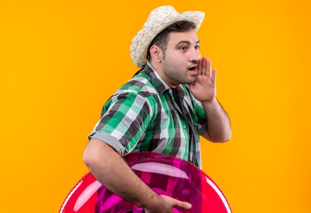 オレンジ色の壁の上に立っている口の近くで誰かを叫んだり、呼び出したりする膨脹可能なリングを保持しているチェックシャツと夏の帽子の若い旅行者
