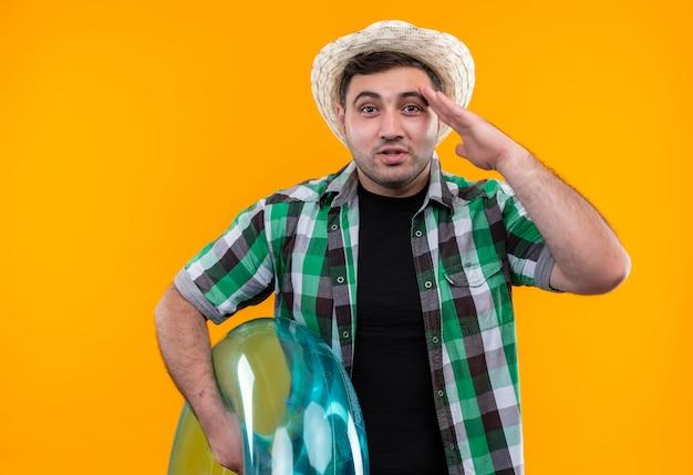 Молодой путешественник в клетчатой рубашке и летней шляпе держит надувное кольцо, улыбаясь и салютуя, стоя над оранжевой стеной