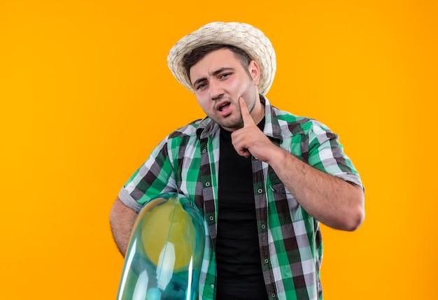 체크 셔츠와 오렌지 벽 위에 서있는 잠겨있는 표정으로 풍선 반지를 들고 여름 모자에 젊은 여행자 남자