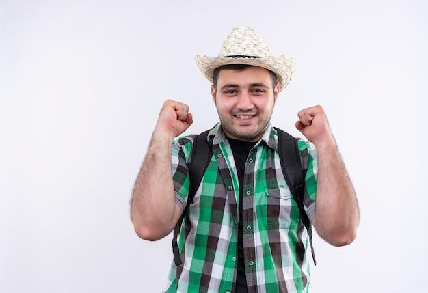 チェックシャツと夏の帽子をかぶった若い旅行者の男は、白い壁の上に立って幸せで興奮した拳を握りしめます。
