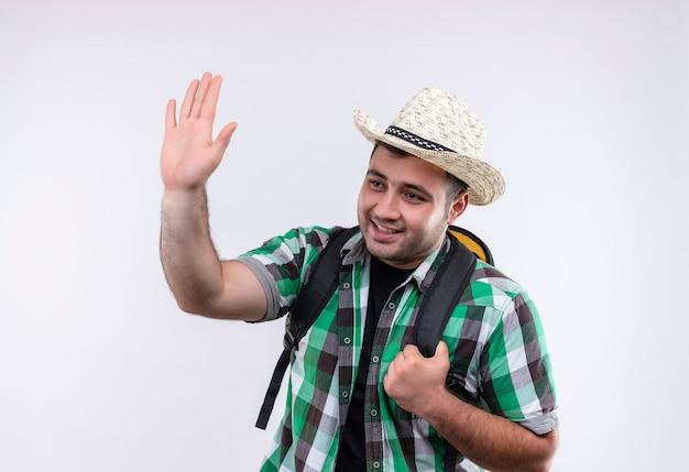 Молодой путешественник в клетчатой рубашке и летней шляпе с рюкзаком весело улыбается и машет рукой, стоящей над белой стеной