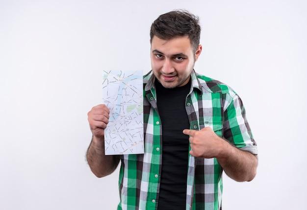 Молодой путешественник в клетчатой рубашке держит карту, указывая пальцем на нее, выглядит уверенно, стоя над белой стеной