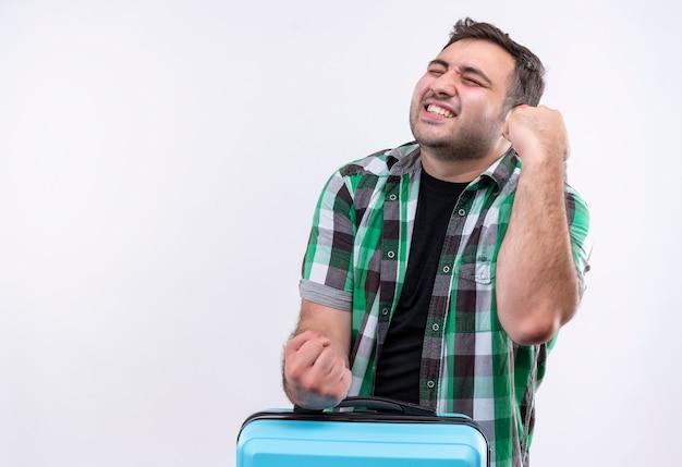 白い壁の上に立って彼の成功を喜んでスーツケースクレイジー幸せな握りこぶしを保持しているチェックシャツの若い旅行者の男