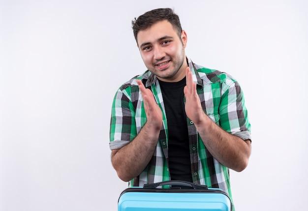Молодой путешественник в клетчатой рубашке держит чемодан счастливой и позитивной улыбкой и аплодирует, стоя над белой стеной