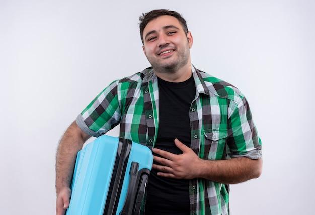 白い壁の上に立って幸せで前向きな笑顔のスーツケースを保持しているチェックシャツの若い旅行者の男