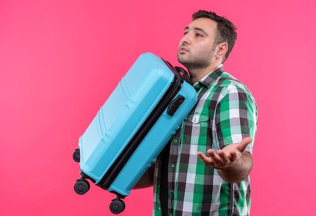 Молодой путешественник в клетчатой рубашке держит чемодан в замешательстве и неуверенно стоит над розовой стеной