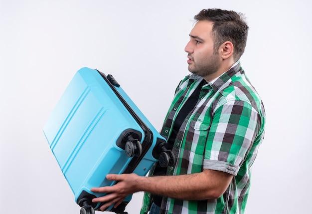 白い壁の上に立って混乱して脇を見てスーツケースを保持しているチェックシャツを着た若い旅行者の男
