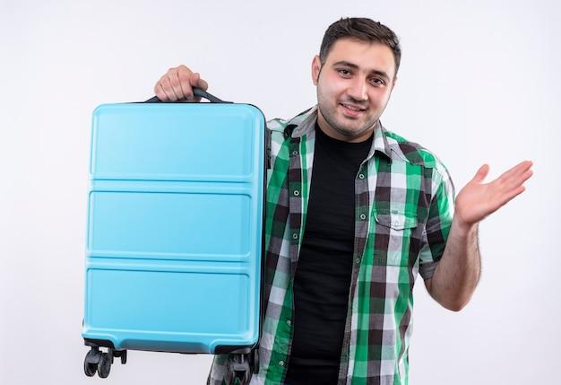 Молодой путешественник в клетчатой рубашке держит чемодан в замешательстве, разводя рукой в сторону, улыбаясь, стоя над белой стеной
