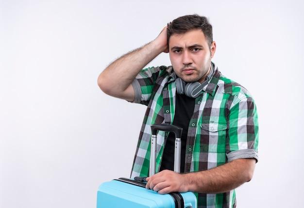 Молодой путешественник в клетчатой рубашке держит чемодан, выглядит неуверенным и смущенным, почесывая голову, стоя над белой стеной
