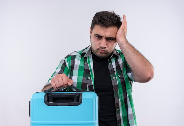 Молодой путешественник в клетчатой рубашке держит чемодан, выглядит неуверенным и смущенным, трогает его голову, надувая щеки, стоя над белой стеной