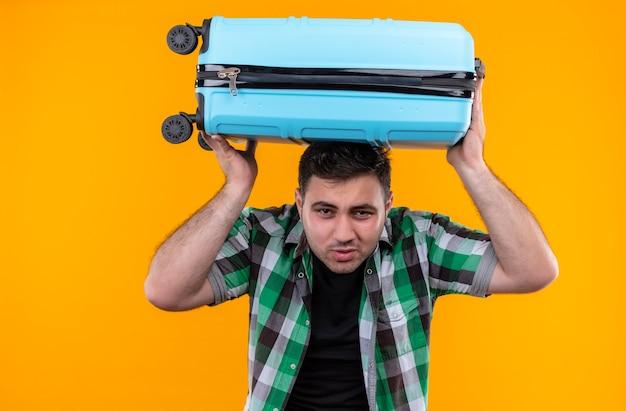 Молодой путешественник в клетчатой рубашке, держащий чемодан на голове, выглядит усталым с раздраженным выражением лица, стоя у оранжевой стены