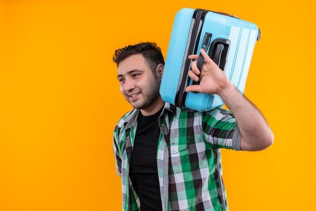オレンジ色の壁の上に立っている幸せそうな顔で笑って彼の肩にスーツケースを保持しているチェックシャツの若い旅行者の男