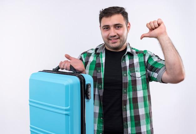 Молодой путешественник в клетчатой рубашке держит чемодан, указывая пальцем на себя с уверенной улыбкой на лице, стоя над белой стеной